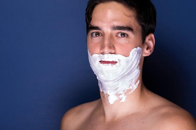 Homem adulto com creme de barbear no rosto