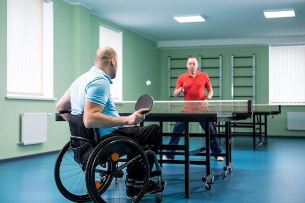 Homem adulto com deficiência em cadeira de rodas joga tênis de mesa com seu treinador