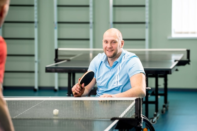 Homem adulto com deficiência em cadeira de rodas jogando tênis de mesa