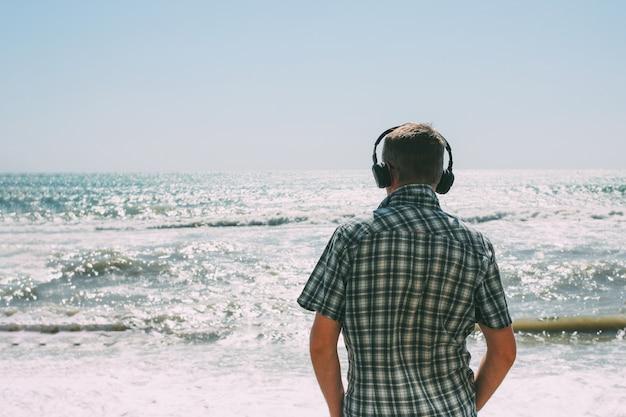 Homem adulto com fones de ouvido, olhando para o mar tempestuoso