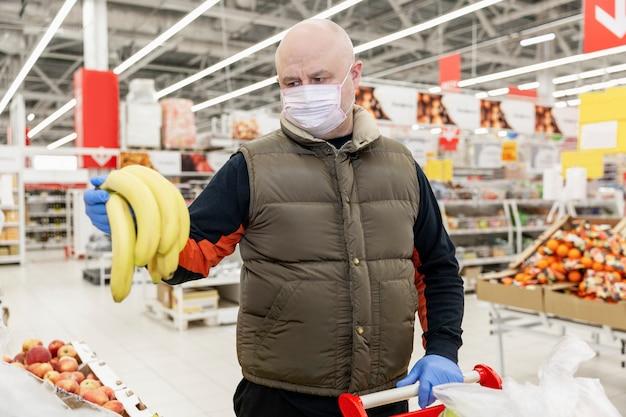Homem adulto com luvas e uma máscara em segurar bananas no corredor de frutas em um supermercado. compras conscientes durante o surto de vírus.