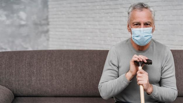 Homem adulto com máscara facial segurando muletas