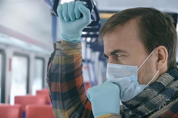 Homem adulto com máscara protetora médica e luvas tosse dentro de transportes públicos