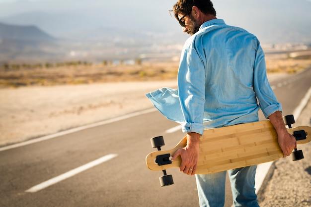 Homem adulto com mesa de prancha longa caminhando em uma longa rua de asfalto - conceito de pessoas modernas alternativas e transporte gratuito para viagens - pessoas ativas ao ar livre