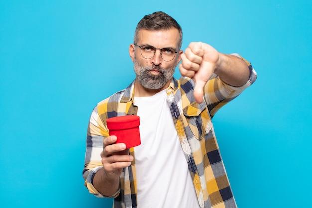 Homem adulto com raiva, aborrecido, desapontado ou descontente, mostrando o polegar para baixo com um olhar sério