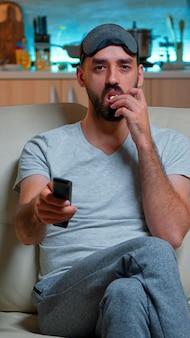 Homem adulto comendo pipoca em frente à televisão
