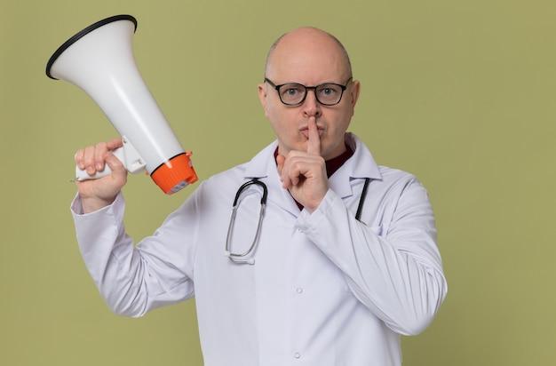 Homem adulto confiante com óculos em uniforme de médico com estetoscópio segurando um alto-falante e fazendo gesto de silêncio