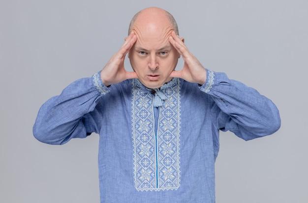 Homem adulto confiante de camisa azul, segurando a cabeça e olhando