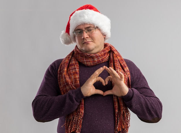 Homem adulto confiante usando óculos e chapéu de papai noel com lenço no pescoço fazendo sinal de coração isolado na parede branca