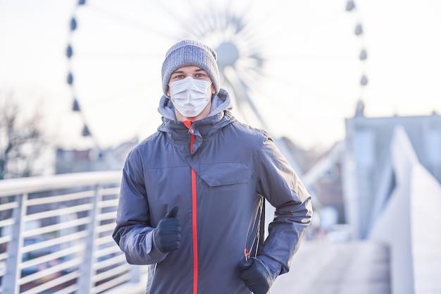 Homem adulto correndo na cidade mascarado durante a pandemia de bloqueio
