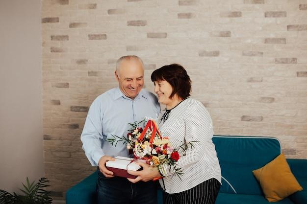 Homem adulto dando um presente surpresa e flores para sua amada esposa no dia do aniversário dela.