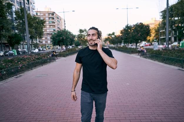 Homem adulto de cabelos compridos caminhando na rua enquanto faz uma ligação comercial