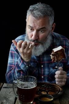 Homem adulto de cabelos grisalhos brutal louco por mostarda e cerveja, feriado, festival, oktoberfest ou dia de são patrício