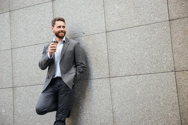 Homem adulto de terno cinza e camisa branca encostado na parede de granito, olhando de lado para copyspace enquanto bebe café para viagem