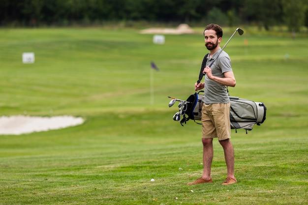 Homem adulto de tiro completo no campo de golfe