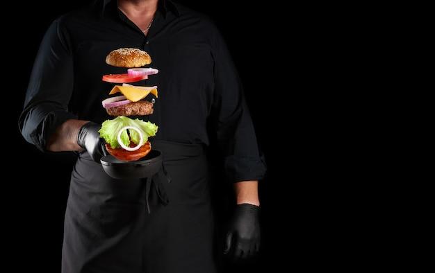 Homem adulto de uniforme preto segurando uma frigideira redonda de ferro fundido com ingredientes de cheeseburguer congelados