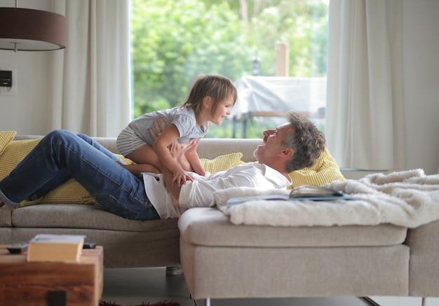 Homem adulto deitado no sofá brincando com seu filho sob o sol através das janelas