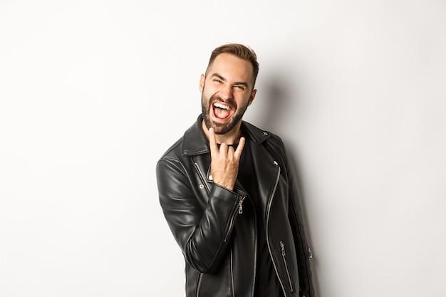 Homem adulto descolado em uma jaqueta de couro preta, mostrando rock no gesto e na língua, curtindo o festival de música, em pé