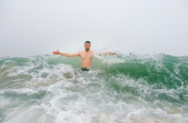 Homem adulto desfrutando no mar tempestuoso e frio.