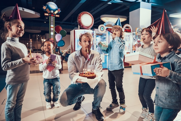 Homem adulto e crianças pequenas comemorando aniversário