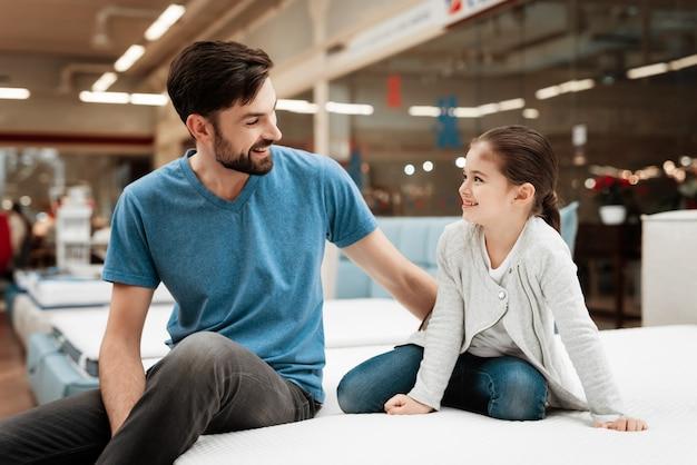 Homem adulto e menina de sorriso na cama na loja.