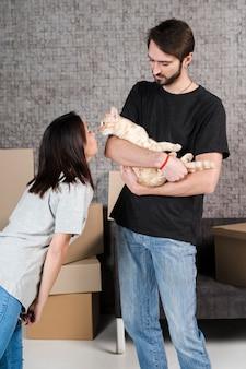 Homem adulto e mulher acariciando gato de família