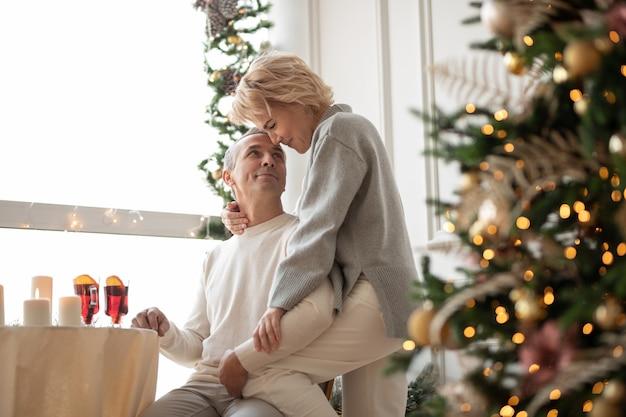 Homem adulto e mulher se abraçando perto da mesa festiva no corredor com uma árvore de natal