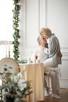 Homem adulto e mulher se abraçando perto da mesa festiva no corredor