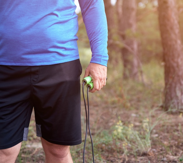 Homem adulto em roupas azuis, segurando uma corda de pular para praticar esportes
