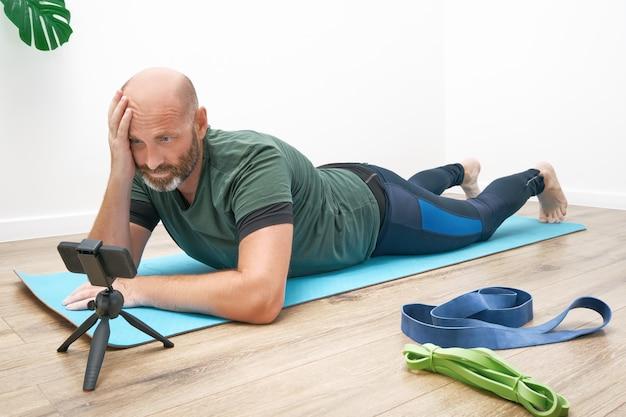 Homem adulto em roupas esportivas está pasmosamente estudando exercícios na frente de um smartphone durante um treino online.