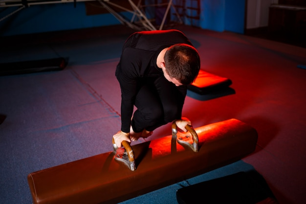 Homem adulto em roupas esportivas fazendo exercícios em aparelhos de ginástica na academia de acrobacia