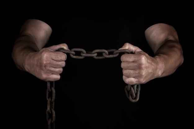 Homem adulto em roupas pretas fica na posição vertical com músculos tensos e mantém uma corrente de metal enferrujada