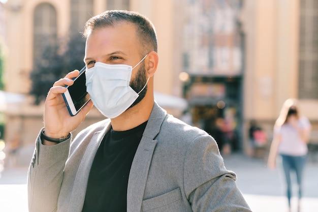 Homem adulto em terno cinza casual com máscara e distância social