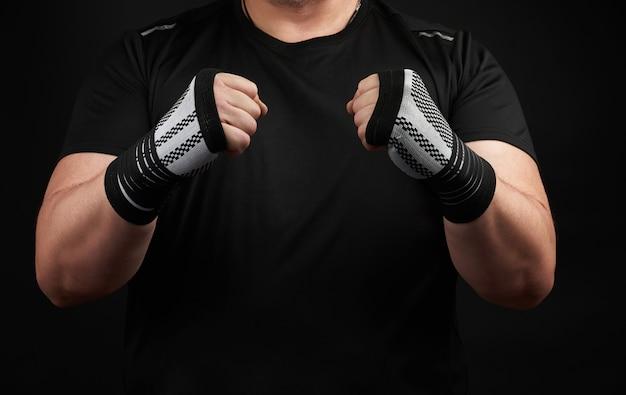 Homem adulto em um uniforme preto e braços musculosos fica em uma postura esportiva, mantém uma bandagem elástica de esportes