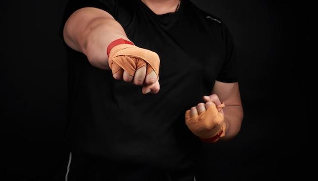 Homem adulto em um uniforme preto e braços musculosos fica em uma postura esportiva