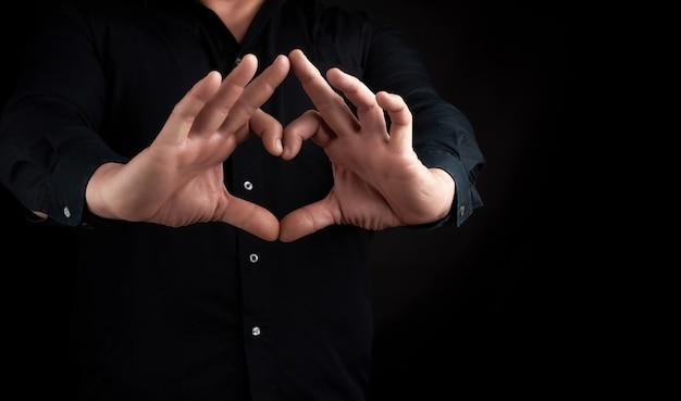 Homem adulto em uma camisa preta mostra as mãos um gesto de coração no escuro