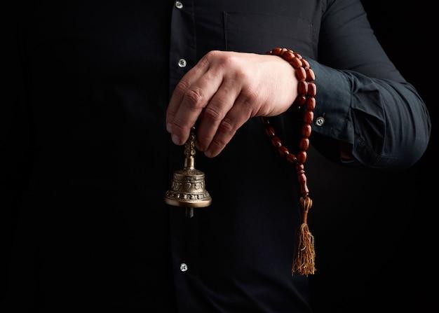 Homem adulto em uma camisa preta segura um sino ritual de cobre tibetano