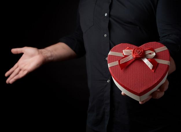 Homem adulto em uma camisa preta segura uma caixa de papelão vermelha em forma de um coração com um laço