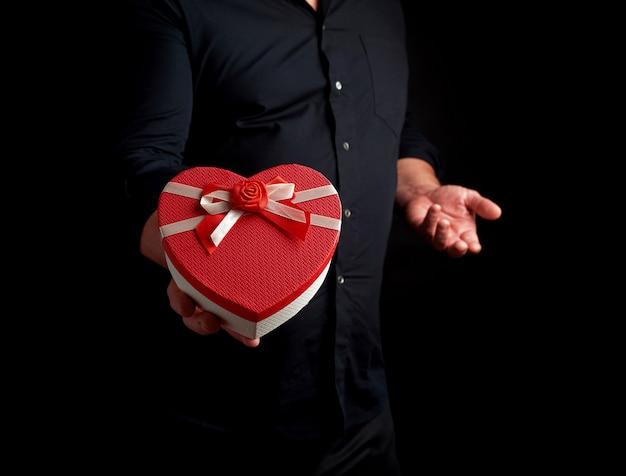 Homem adulto em uma camisa preta segura uma caixa de papelão vermelha na forma de um coração com um laço em um fundo escuro