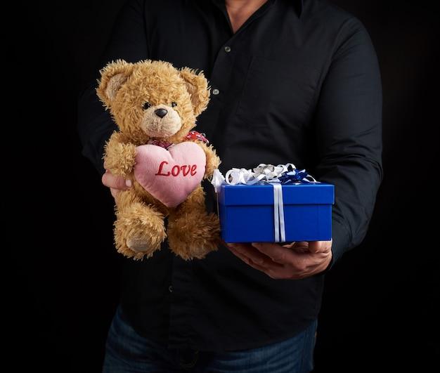 Homem adulto em uma camisa preta segura uma caixa quadrada azul amarrada com uma fita branca