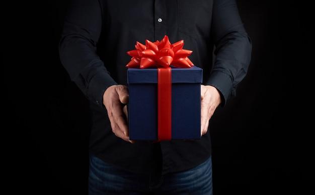Homem adulto em uma camisa preta segura uma caixa quadrada azul com um laço vermelho amarrado