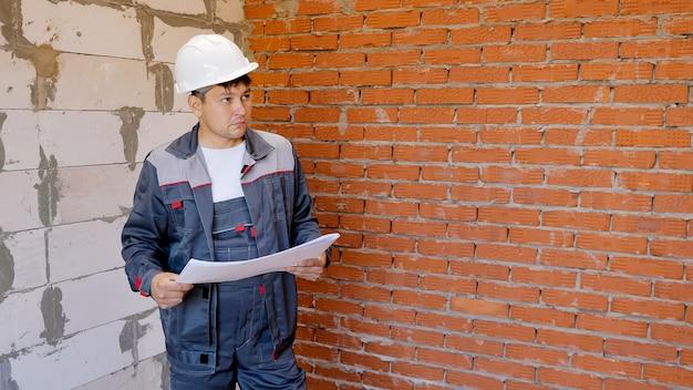 Homem adulto em uma sala vazia segurando plantas de papel do prédio em construção e monitorando o interior