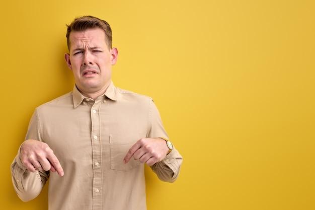 Homem adulto emocional infantil pede para prestar atenção, apontando o dedo para baixo
