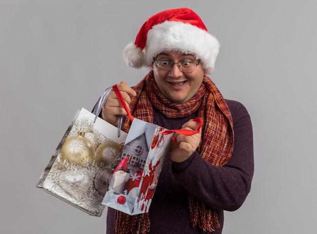 Homem adulto empolgado de óculos e chapéu de papai noel com lenço no pescoço segurando sacolas de presente de natal abrindo uma delas, isolada na parede branca.