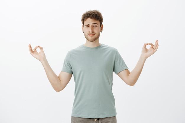 Homem adulto engraçado sem foco com cerdas nos brincos, espiando com um olho enquanto está de pé com as mãos abertas em gesto zen e praticando ioga ou meditação