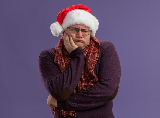 Homem adulto entediado de óculos e chapéu de papai noel com lenço no pescoço e mão no queixo olhando para o lado isolado na parede roxa