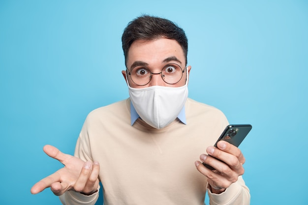 Homem adulto envergonhado e estupefato olha chocado, usa máscara para evitar ser infectado por coronavírus permanece seguro durante quarentena em casa usa telefone celular