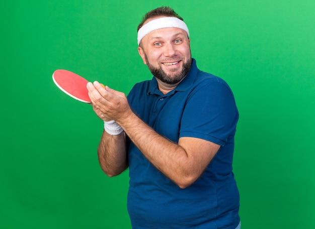 Homem adulto eslavo e esportivo sorridente usando bandana e pulseiras segurando uma bola de pingue-pongue e raquete isolada na parede verde com espaço de cópia