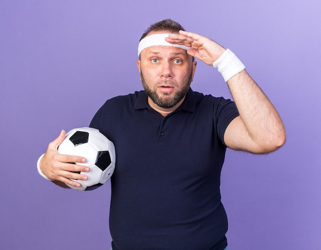 Homem adulto eslavo e esportivo surpreso usando bandana e pulseiras, segurando a palma da mão na testa e segurando uma bola isolada na parede roxa com espaço de cópia