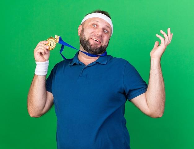 Homem adulto eslavo e esportivo surpreso usando bandana e pulseiras segurando uma medalha de ouro isolada na parede verde com espaço de cópia